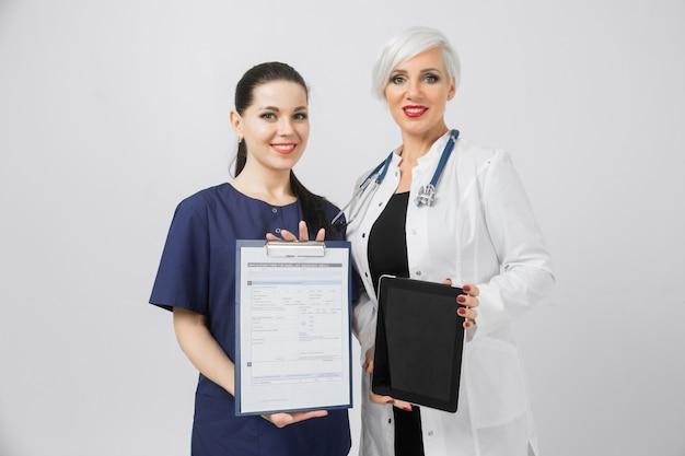 Twee vrouwelijke artsen met tablet en blad met geïsoleerde analyse in handen