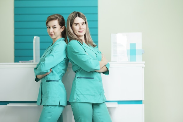 Twee vrouwelijke artsen of verpleegsters die de camera bekijken.