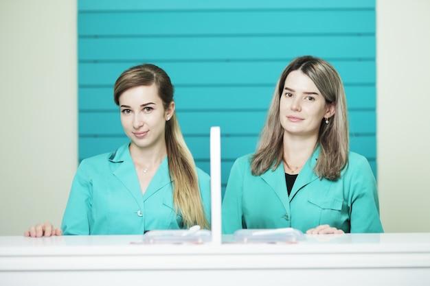 Twee vrouwelijke artsen of verpleegsters in de receptie van het ziekenhuis.