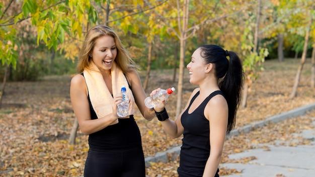 Twee vrouwelijke atletische teamgenoten lachen samen tijdens een pauze tijdens de training terwijl ze wat verfrissend flessenwater drinken