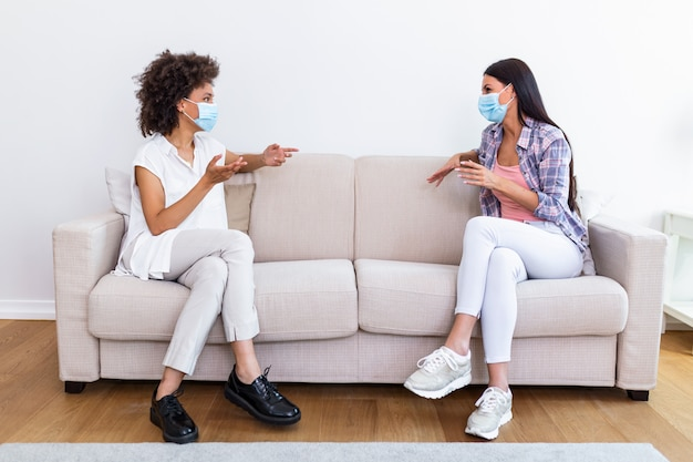 Twee vrouwelijke beste vrienden die op sociale afstand zitten, een gezichtsmasker dragen en op de bank praten, om te voorkomen dat covid 19 coronavirus-infectie zich verspreidt.
