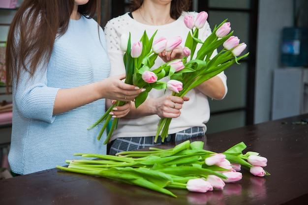 Twee vrouwelijke bloemistontwerpers die vakantietulpboeketten maken bij bloemenwinkel. bloemendecoratieproces
