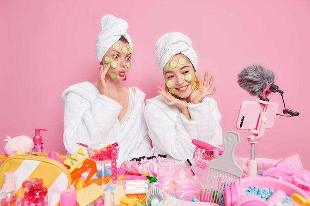 Twee vrouwelijke bloggers laten zien hoe je een natuurlijk gezichtsmasker kunt maken, plakjes komkommer op het gezicht kunt aanbrengen en vlog-video kunt opnemen op een smartphone. draag witte zachte badjassen en handdoeken boven je hoofd geïsoleerd over een roze muur