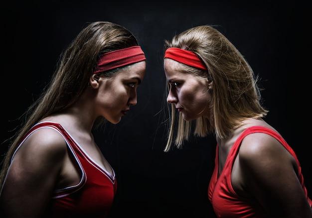 Twee vrouwelijke boksers in rode sportkleding staan oog in oog. bestrijding van sport en krijgskunst concept