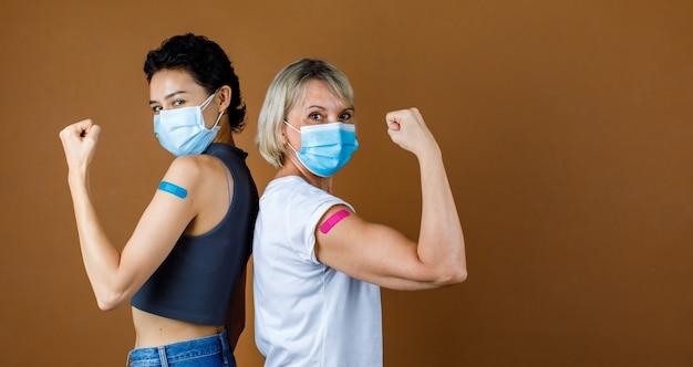 Twee vrouwelijke burgers van het geslacht dragen een gezichtsmasker terwijl ze naar de camera kijken, op elkaar leunen, de vuist omhoog houden en sterke spieren met kleurrijke pleister samen tonen na vaccinatie.