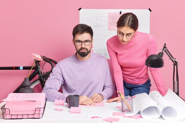 Twee vrouwelijke en mannelijke professionele architecten werken samen en hersenstrom in coworking-ruimte poseren bij dekstop werken op schaal modern huis bereiden zich voor om presentatie te geven aan de klant, bespreken en genereren ideeën
