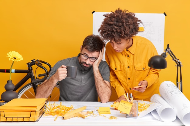 Twee vrouwelijke en mannelijke zakenpartners delen informatie voor het creëren van een nieuw project, aandachtig gefocust op kranten werken samen voor een nieuw gebouw bluerpints poseren in een coworking-ruimte. samenwerkingsconcept