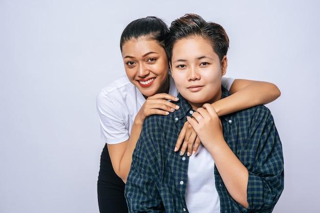 Twee vrouwelijke geliefden permanent en knuffelen van achteren.