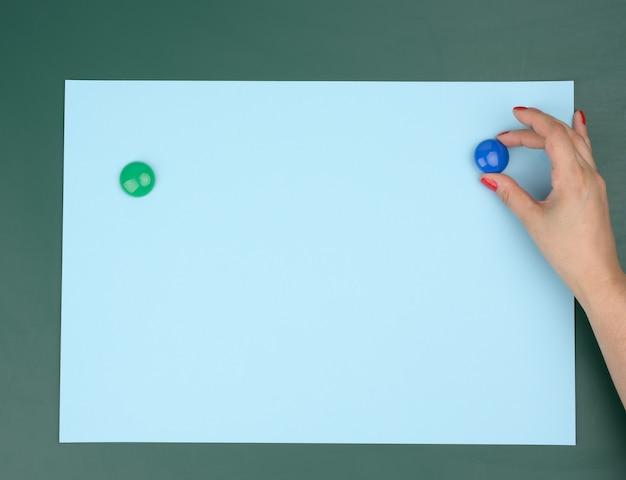 Twee vrouwelijke handen bevestigen een blauw blanco vel papier op een magnetisch bord, plaats voor een inscriptie