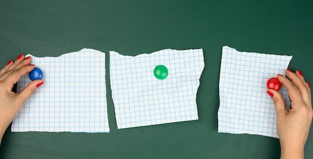 Twee vrouwelijke handen bevestigen witte blanco vellen papier in een doos op een groen magneetbord, een plek voor een inscriptie
