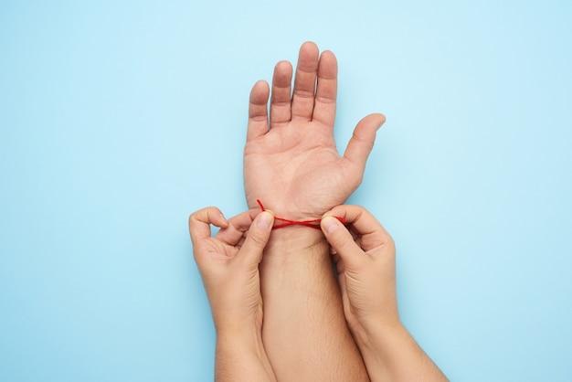 Twee vrouwelijke handen binden een rode wollen draad om de pols van een mannenhand bovenaanzicht