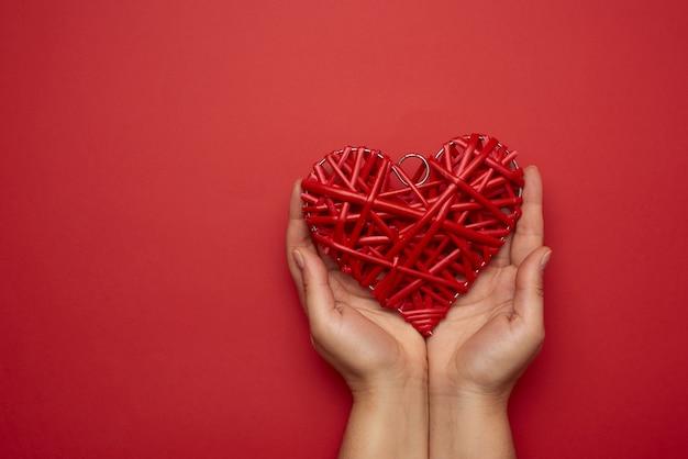 Twee vrouwelijke handen die een rood rieten hart, liefdeconcept, exemplaarruimte houden