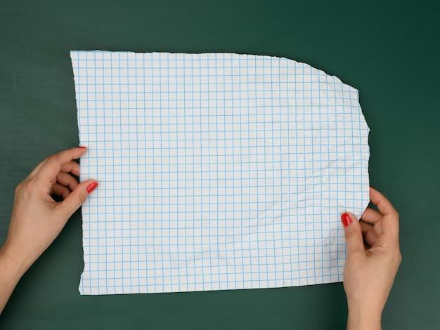 Twee vrouwelijke handen houden blanco vellen papier vast in een doos, een plek voor een inscriptie