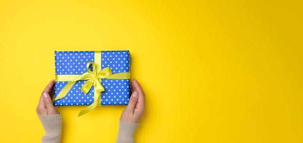 Twee vrouwelijke handen houden een blauwe geschenkdoos vast op een gele achtergrond, gelukkig verjaardagsconcept, kopieer ruimte