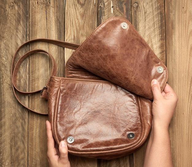 Twee vrouwelijke handen houden een bruine leren tas op een grijze houten achtergrond