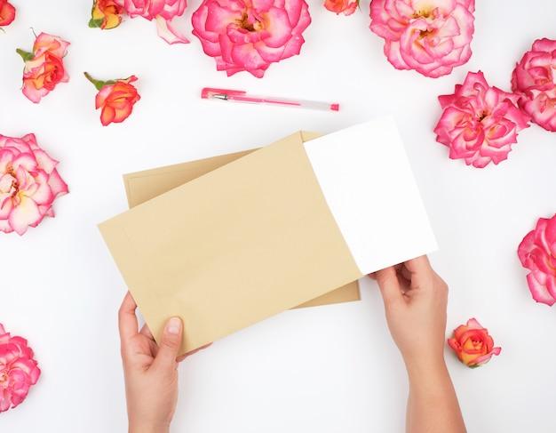 Twee vrouwelijke handen houden een bruine papieren envelop