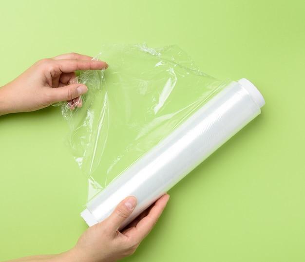 Twee vrouwelijke handen houden een rol transparante huishoudfolie voor het verpakken van producten, groene achtergrond