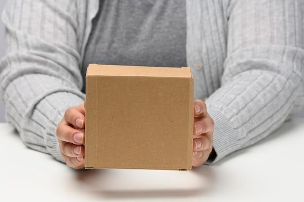 Twee vrouwelijke handen houden een vierkante doos van bruin golfkarton op een witte achtergrond vast, close-up