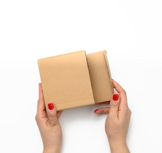 Twee vrouwelijke handen houden een vierkante doos van bruin golfkarton op een witte achtergrond vast