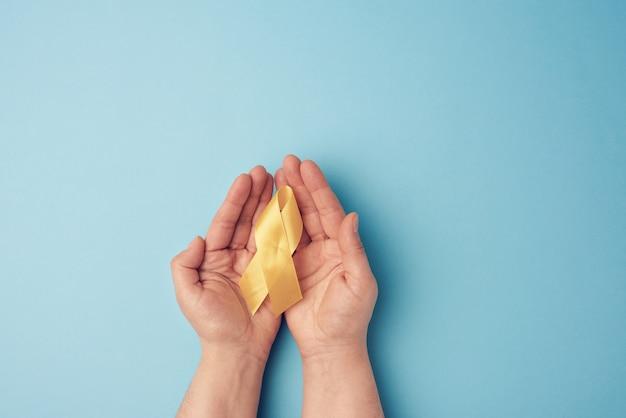 Twee vrouwelijke handen houden in hun handpalmen een geel lint in de vorm van een lus op een blauw oppervlak