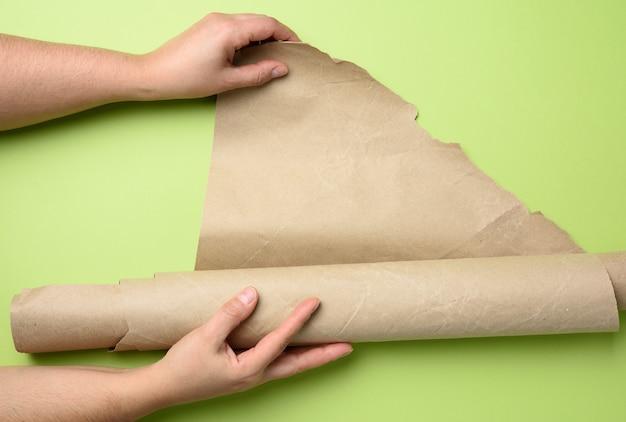 Twee vrouwelijke handen houden opgerold bruin papier vast