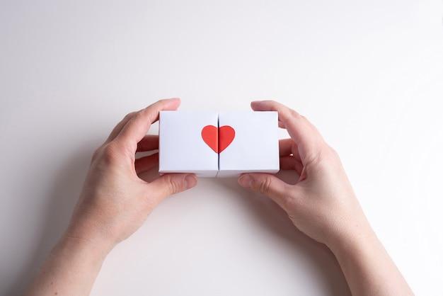 Twee vrouwelijke handen houden twee witte dozen met hart vast.