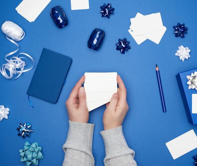 Twee vrouwelijke handen houden witboek blanco visitekaartjes