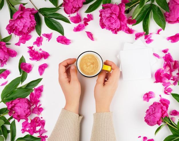 Twee vrouwelijke handen met een gele keramische mok met zwarte koffie