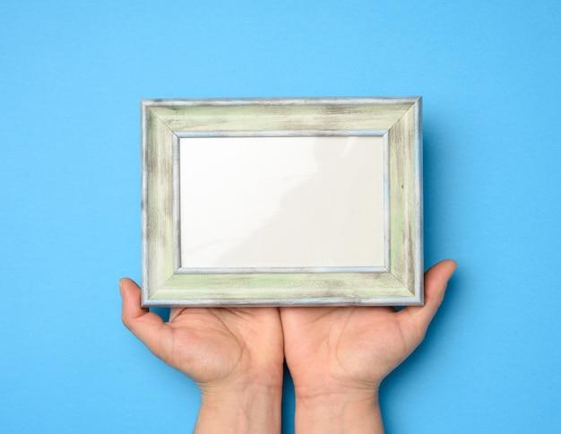 Twee vrouwelijke handen met een rechthoekig leeg houten frame, blauwe achtergrond