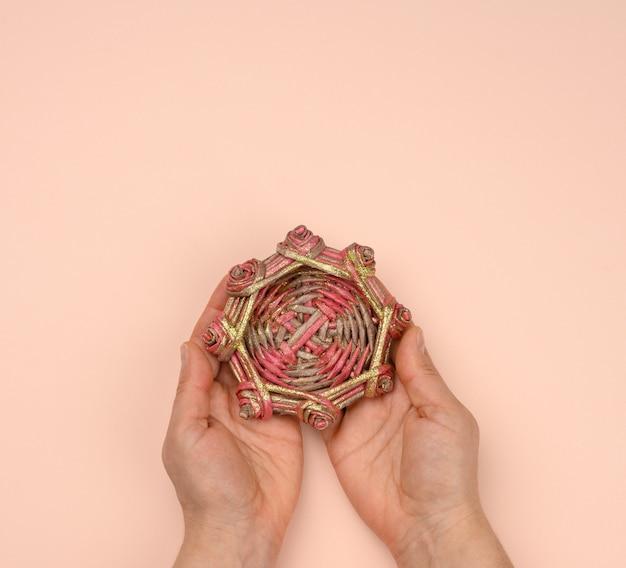 Twee vrouwelijke handen met een rieten houten miniatuur decoratief nest, bovenaanzicht