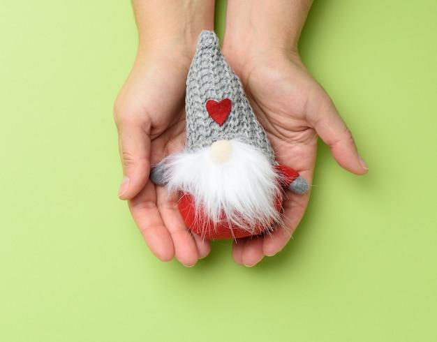 Twee vrouwelijke handen met een traditioneel kerststuk speelgoed