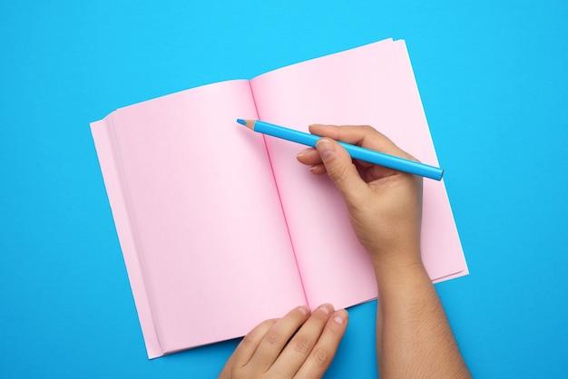 Twee vrouwelijke handen met open kladblok met lege roze lakens, bovenaanzicht