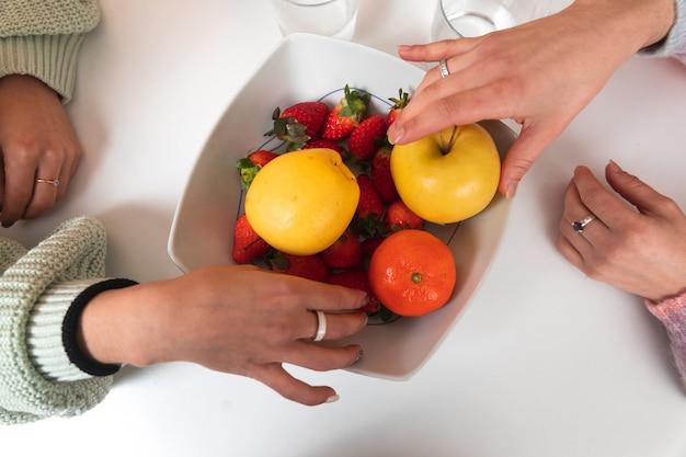 Twee vrouwelijke handen nemen fruit van een bal op een tafel