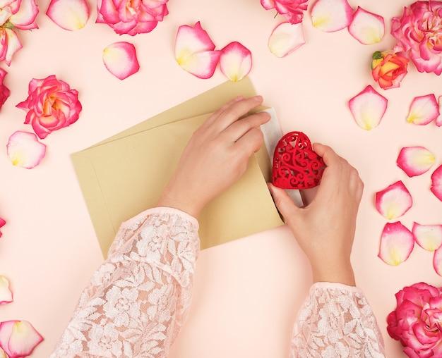 Twee vrouwelijke handen stoppen een rood hart in een bruine papieren envelop
