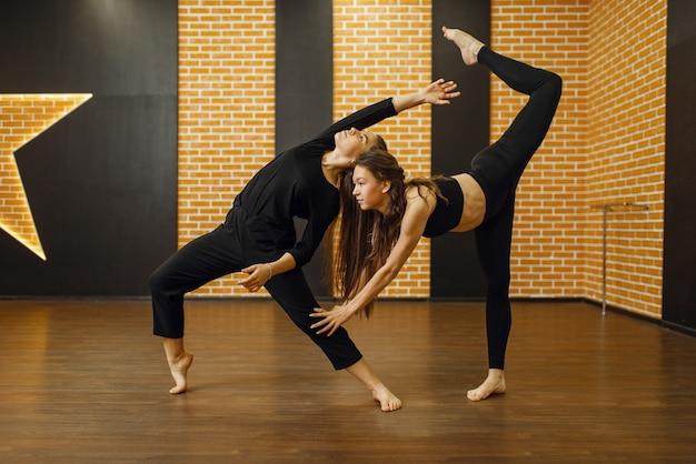 Twee vrouwelijke hedendaagse dansartiesten in studio. dansers trainen in de klas, moderne elegantie dansen, rekoefeningen