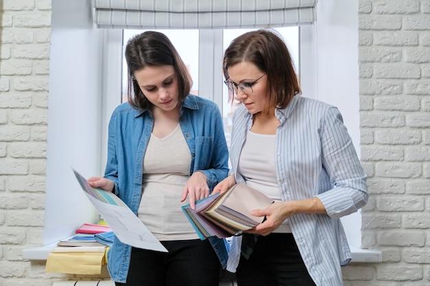Twee vrouwelijke interieurontwerper en klant die stoffen kiezen voor de decoratie van huistextiel, gordijnen