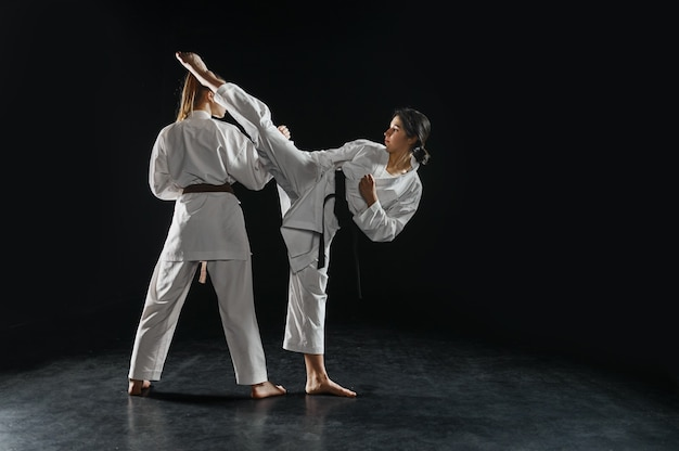 Twee vrouwelijke karateka's in witte kimono, staking in actie. karatevechters op training, vechtsporten, vrouwen die vechten tegen concurrentie