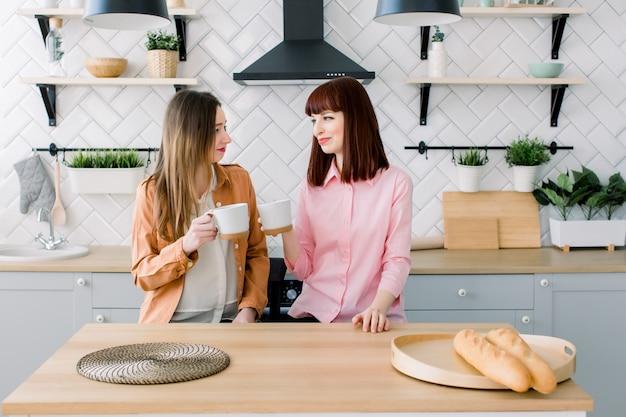 Twee vrouwelijke kaukasische vrienden die koffie in keuken nippen