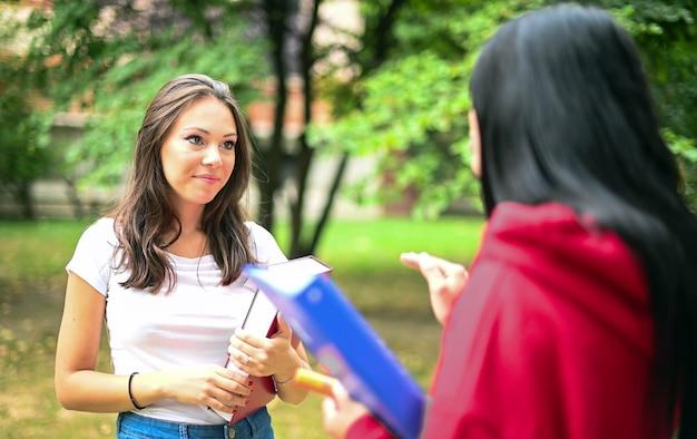 Twee vrouwelijke klasgenoten praten op de binnenplaats van een universiteit
