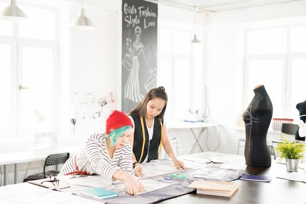 Twee vrouwelijke kleermakers werken in atelier workshop
