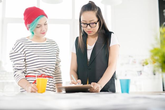Twee vrouwelijke kleermakers werken in atelier