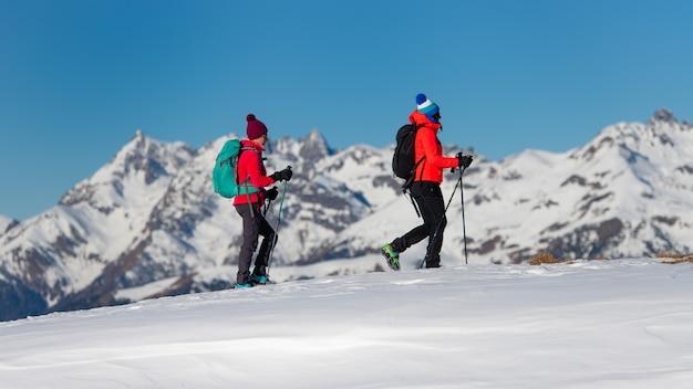 Twee vrouwelijke klimmers tijdens een training lopen in de sneeuw