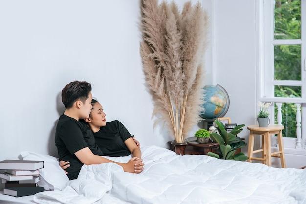 Twee vrouwelijke koppels knuffelden samen in bed.