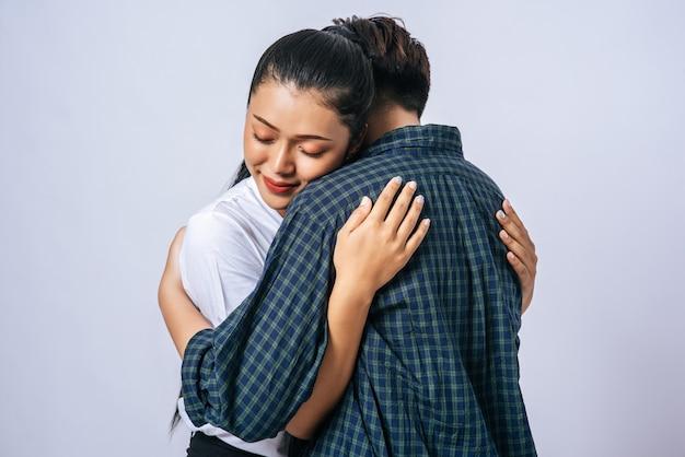 Twee vrouwelijke koppels staan en knuffelen elkaar.