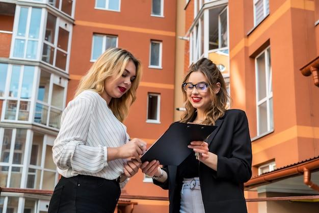 Twee vrouwelijke makelaars die zich buiten dichtbij nieuw huis bevinden, bereiden zich voor op verkoop of huur