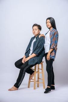 Twee vrouwelijke minnaars grijpen een andere schouder en gaan in een stoel zitten.