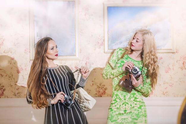 Twee vrouwelijke modellen in modieuze jurken met vintage camera's in vintage interieur