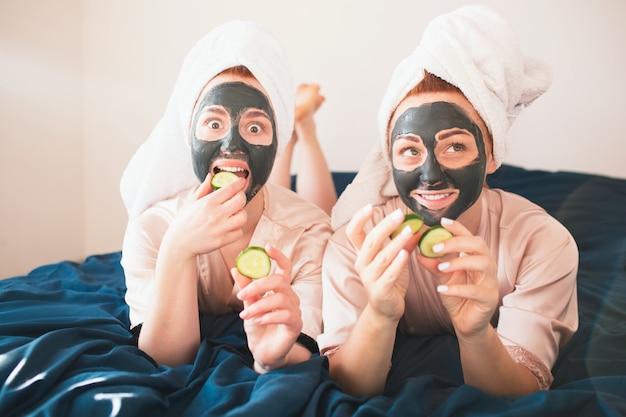 Twee vrouwelijke modellen maken een gezichtsmasker en gebruiken verse groene komkommer