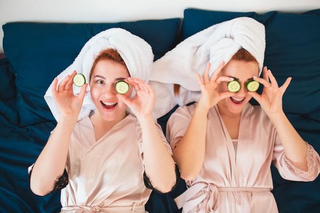 Twee vrouwelijke modellen maken een oogmasker met verse groene komkommer