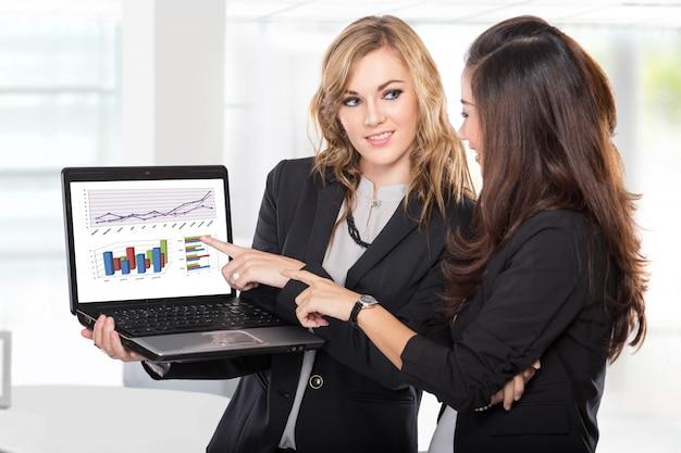 Twee vrouwelijke ondernemers bespreken iets op de laptop